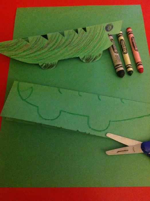 Green paper folded in half, half crocodile body drawn on, then cut out